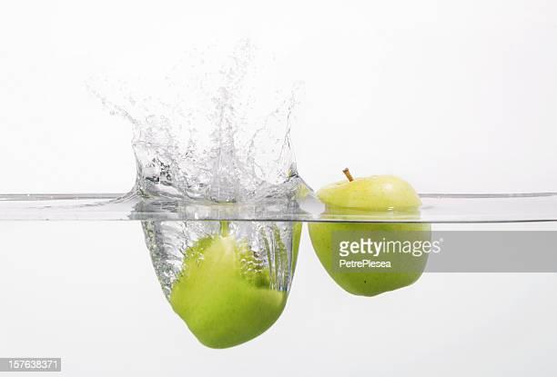 2 apples splashing into the water - drijven stockfoto's en -beelden