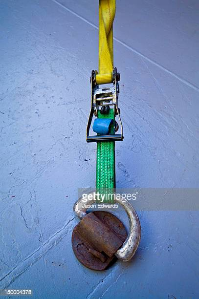 Ratchets fasten straps to a bracket on the floor of a cargo ship hold.