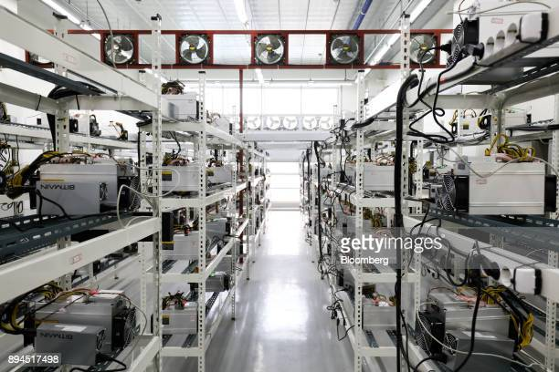 Applicationspecific integrated circuit devices and power units manufactured by Bitmain Technologies Inc sit on shelves at a cryptocurrency mining...