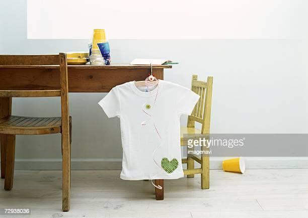Appliqued t-shirt hanging on desk