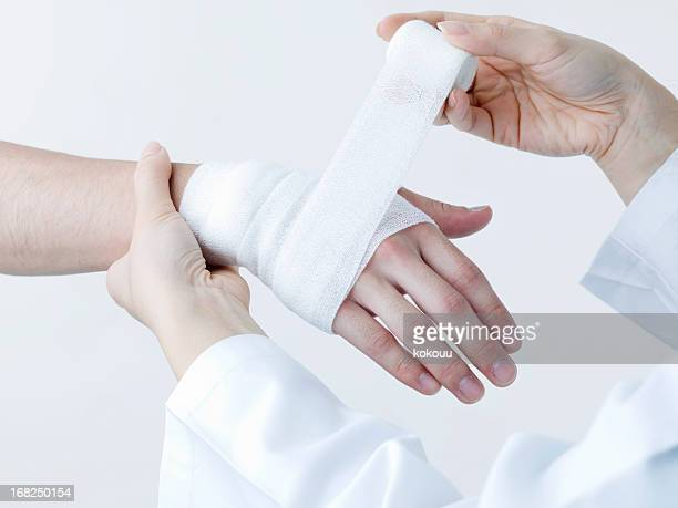 apply a bandage - wounded stock photos and pictures