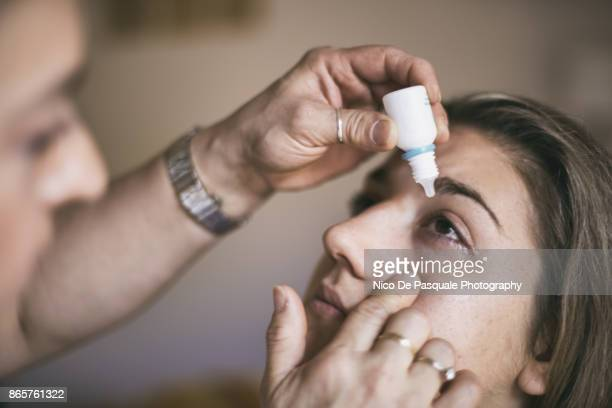 applying eye drops - kin in de hand stock pictures, royalty-free photos & images