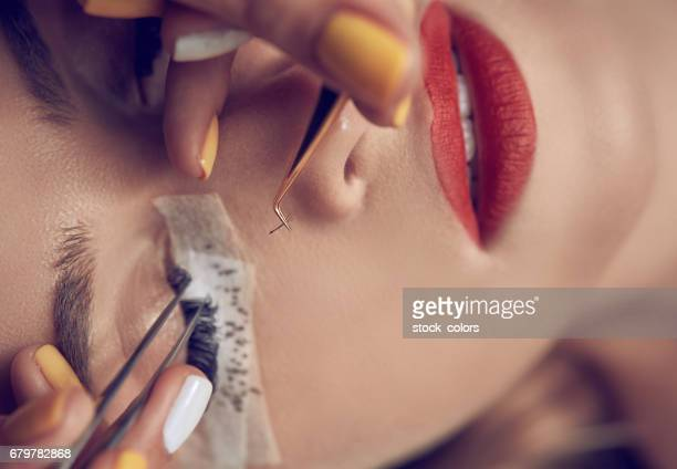 applying false eyelashes - false eyelash stock pictures, royalty-free photos & images