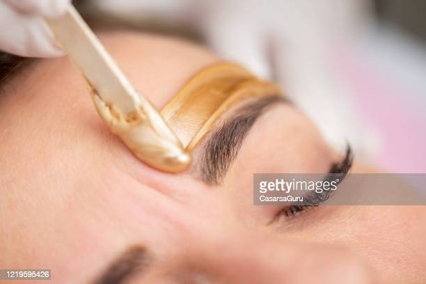 applying gold colored wax with spatula on woman's face - stock photo - mid adult women stock pictures, royalty-free photos & images