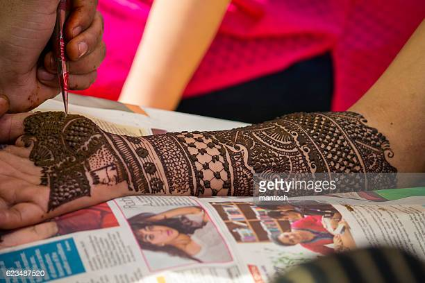 Applying henna on hands of an Indian bride