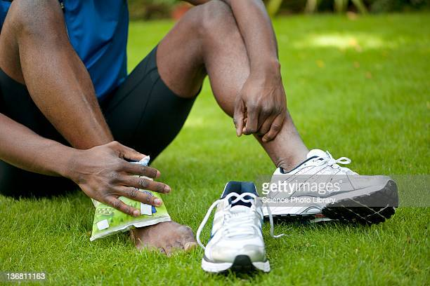 Applying ice pack to injured ankle