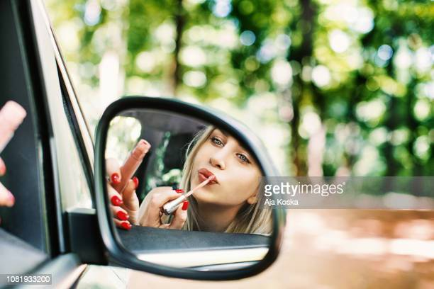 applying make up in the car. - lip gloss stock pictures, royalty-free photos & images