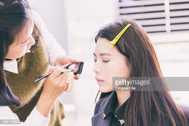 applying makeup to a beautiful girl - visagist stockfoto's en -beelden
