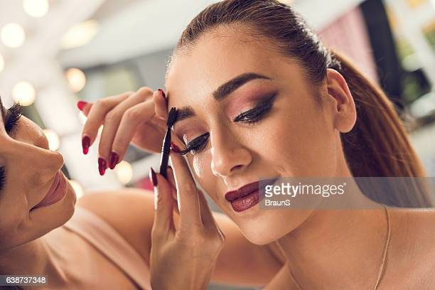 Applying mascara to woman's eyebrow in beauty salon!
