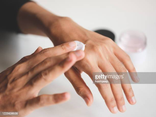 applying moisturising hand cream - back of hand stock pictures, royalty-free photos & images