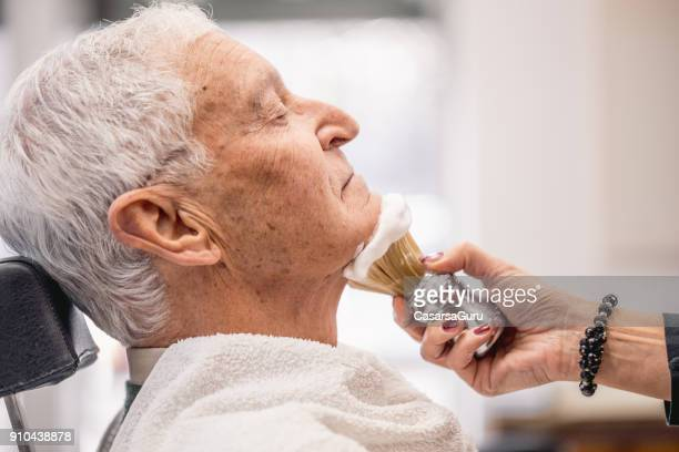 applying shaving cream on senior man side view - grooming product stock photos and pictures