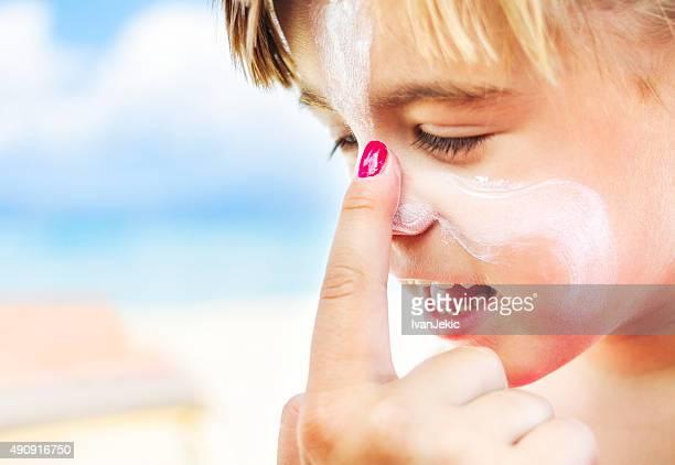 Die Anwendung von Sonnencreme auf Kindes Gesicht am Strand