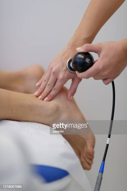 applying tecar therapy on patient's heel - achilles tendon stock pictures, royalty-free photos & images