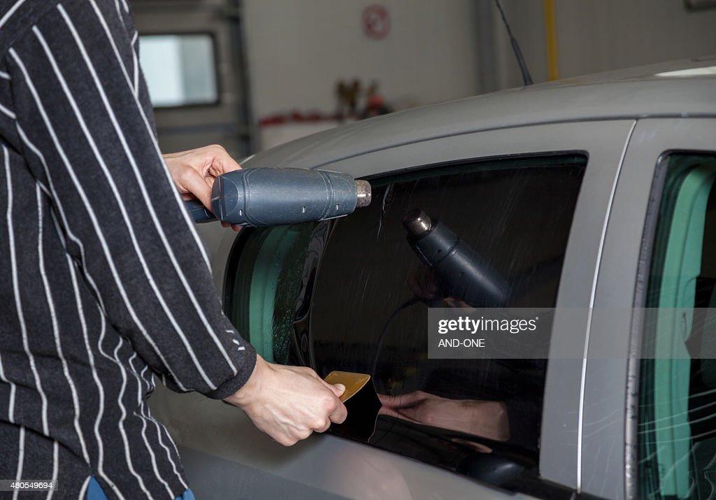 Applying tinting foil on a car window : Stock Photo