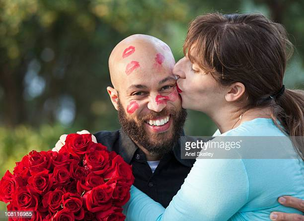 appreciative woman kissing husband all over face - naughty valentine stockfoto's en -beelden