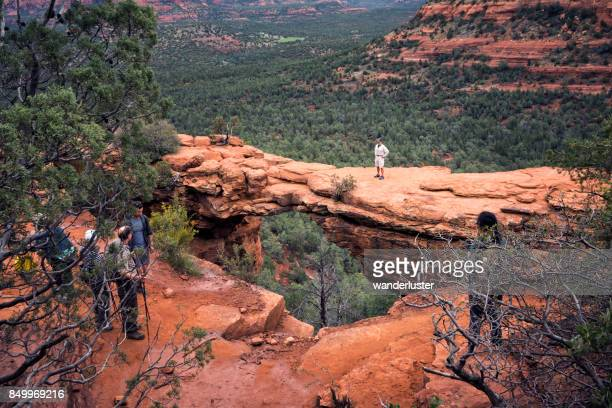 arizona, usa - march 25, 2017: apprehensive adult male stands on the natural limestone archway known as devil's bridge while hiking on a spring day wihile other hikers watch from the safety of the main land in sedona, usa - bermuda triangle stock photos and pictures