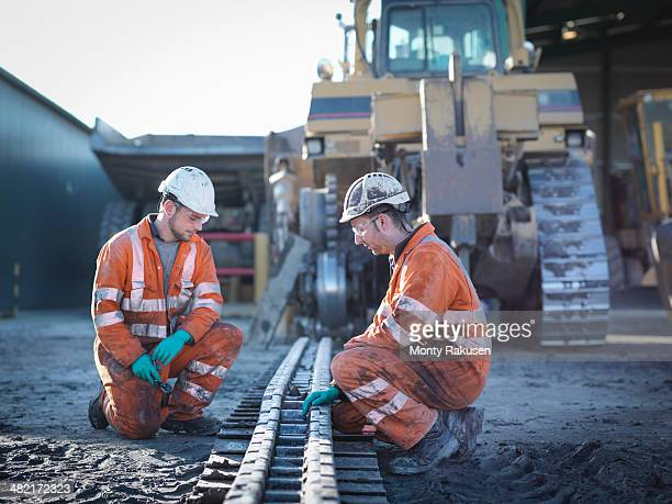 Apprentice and engineer work on machinery in surface coal mine
