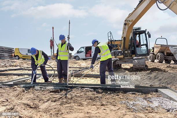 apprentice builders laying concrete foundations on building site - putting stock pictures, royalty-free photos & images