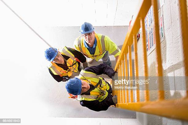 Apprentice builders learning how to climb ladders in training facility