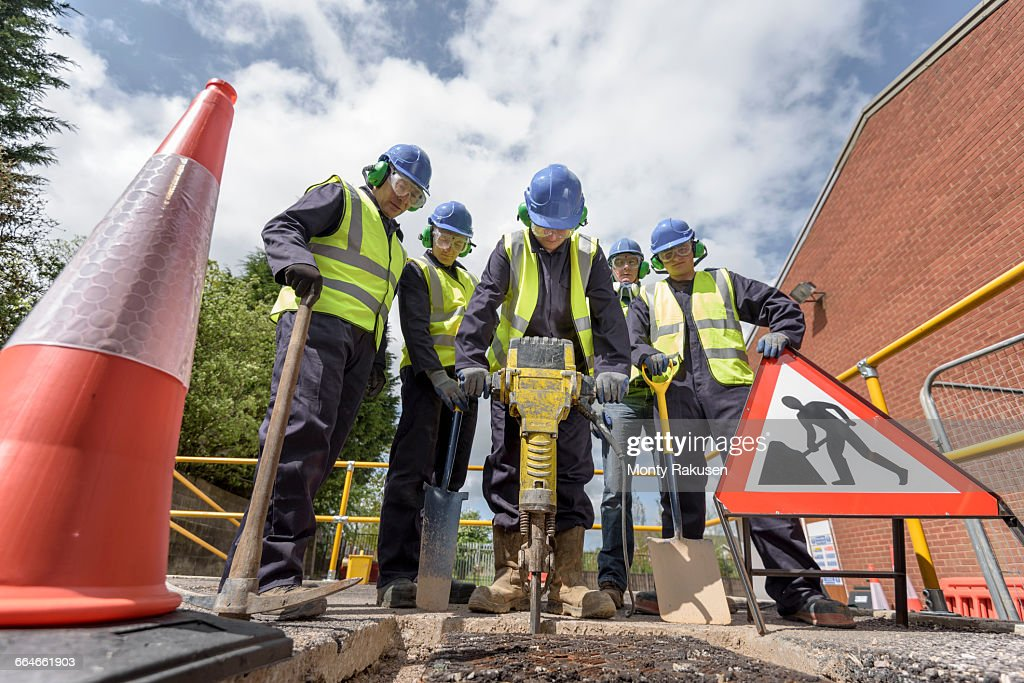 Apprentice builders training with pneumatic drill in training facility : Stock-Foto