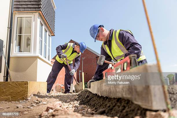 Apprentice builders using digger to lift kerb stones on housing building site
