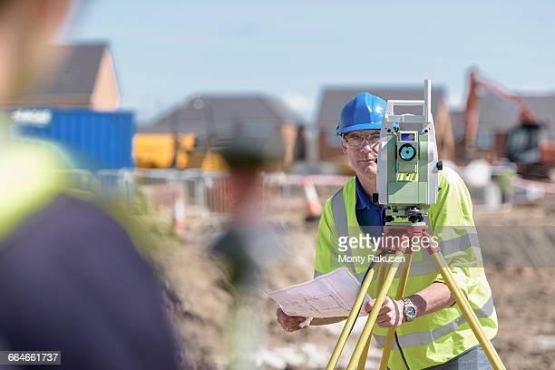 Apprentice builders using theodolite on building site