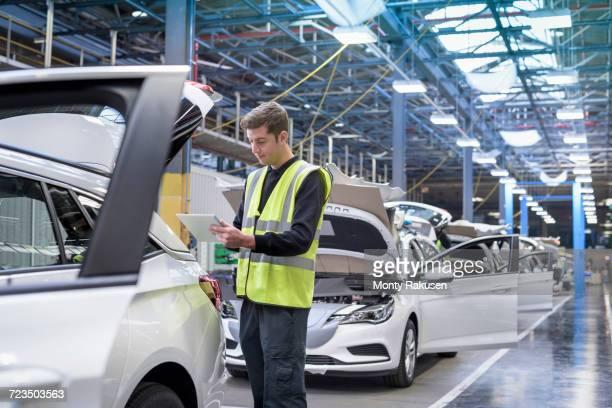 Apprentice car inspector using tablet in car factory