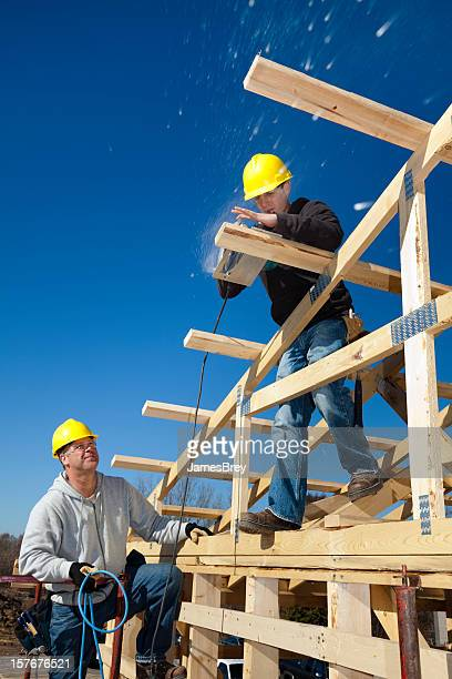Apprentice Carpenter Building House With Supervision