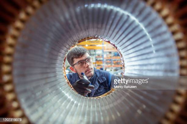 apprentice electrical engineer inspecting winding on generator stator in electrical engineering factory - plant stock pictures, royalty-free photos & images