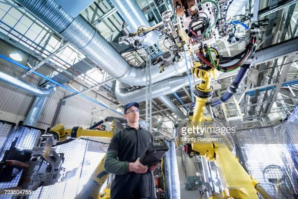 Apprentice engineer adjusting robot in car factory