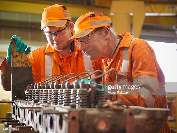 Apprentice engineer and engineer at work