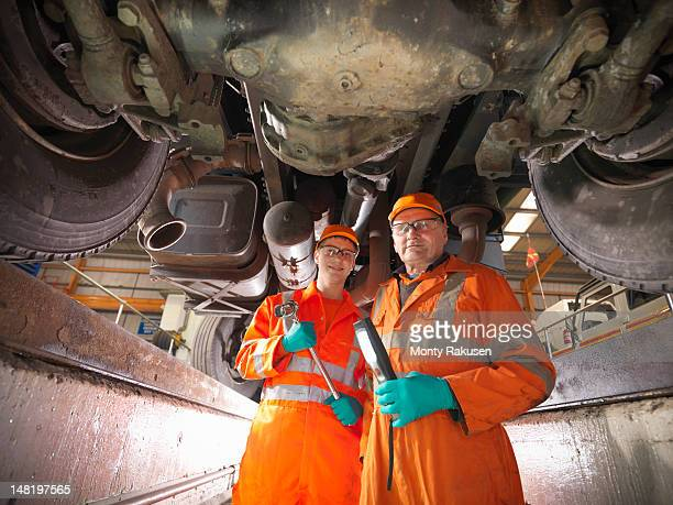 Apprentice engineer and engineer inspecting underneath truck