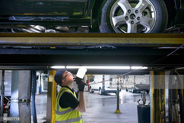 Apprentice engineer holding torch under car on production line in car factory