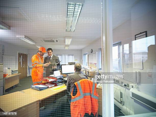 Apprentice engineer in discussion with office workers