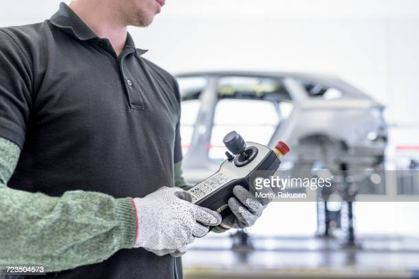 Apprentice engineer measuring car body in car factory, close-up, mid section