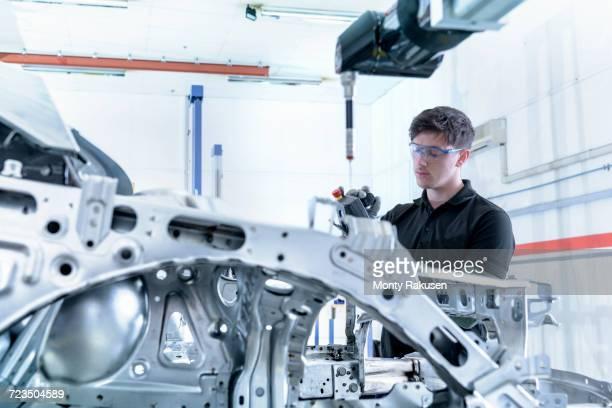 Apprentice engineer measuring car body in car factory
