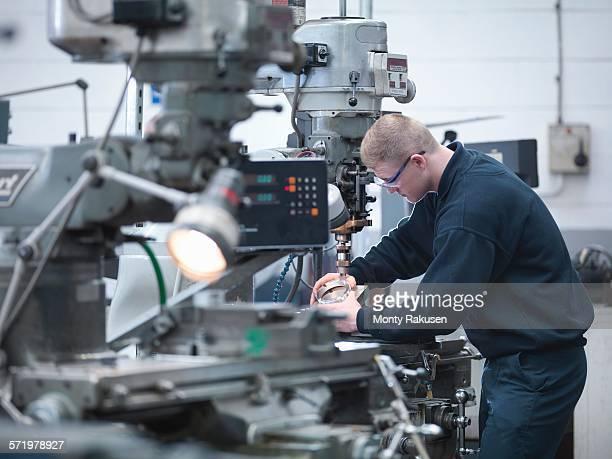 Apprentice engineer on lathe in engineering factory