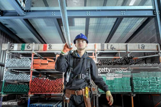Apprentice engineer preparing and setting up scaffolding