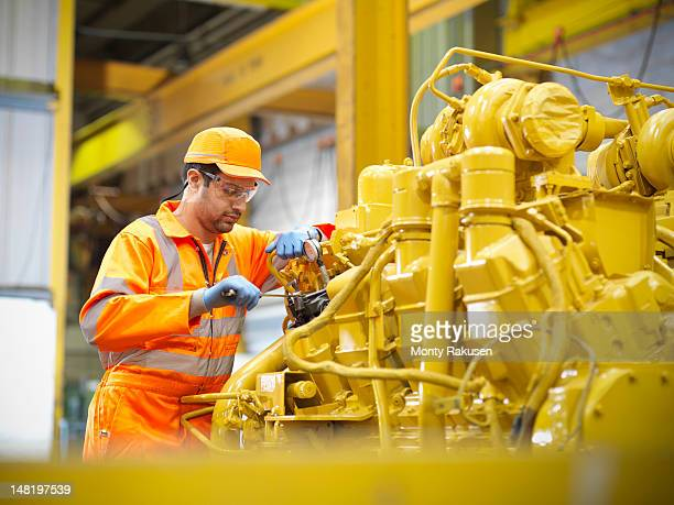 Apprentice engineer working on engine