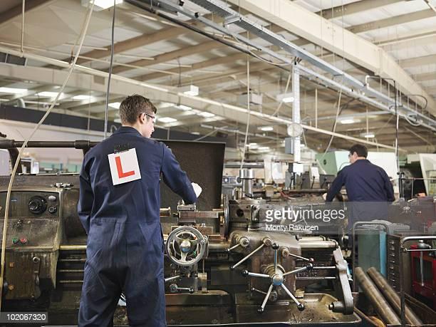Apprentice & Engineer Working On Machine