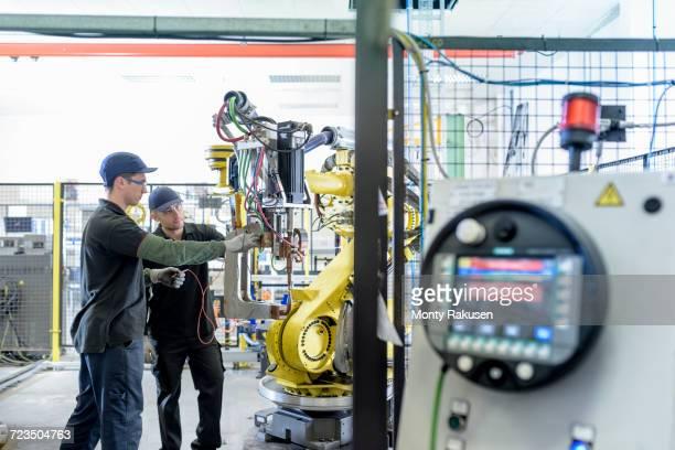 Apprentice engineers adjusting robot in car factory