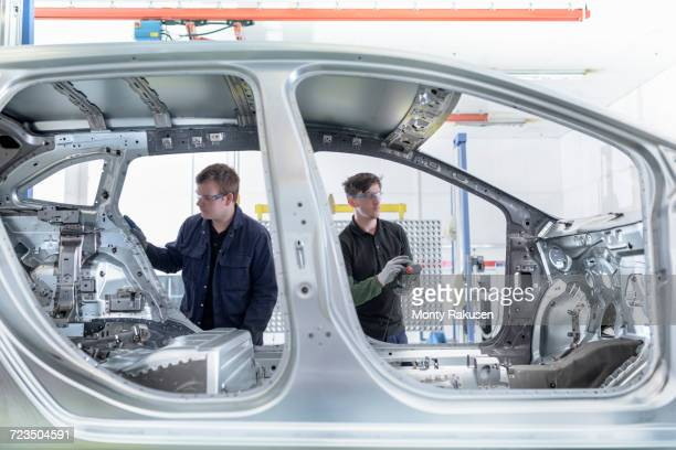 Apprentice engineers measuring car body in car factory