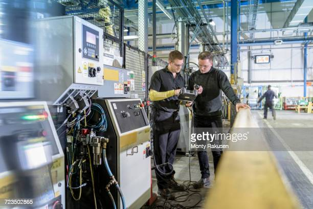 Apprentice engineers on production line in car factory