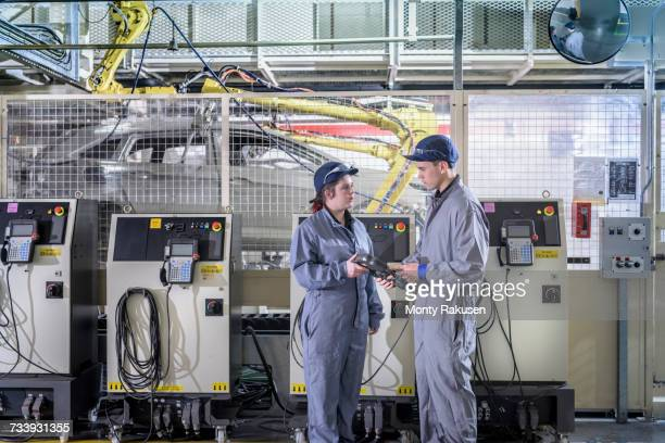 Apprentice engineers with car sealant robot in car factory