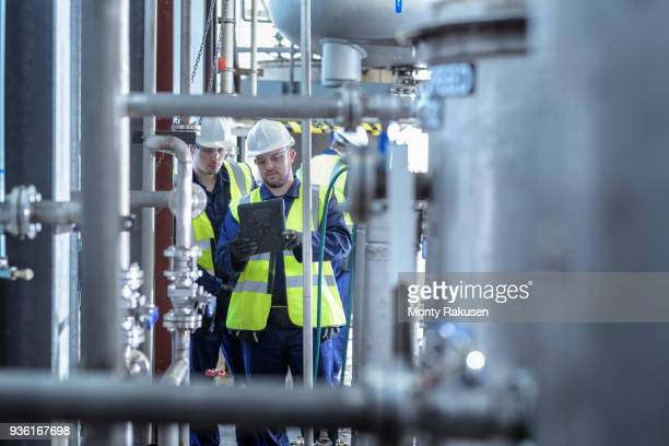 apprentice engineers working on pipeline in industrial product facility - monty rakusen stock photos and pictures