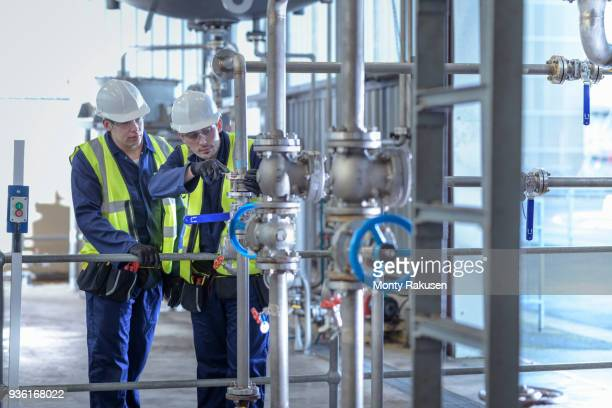 Apprentice engineers working on pipeline in industrial product facility