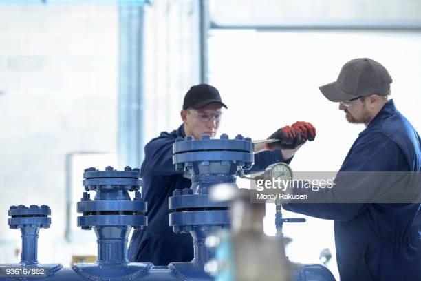 Apprentice engineers working on pipework