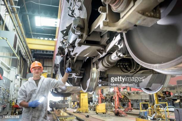 Apprentice locomotive engineer working on locomotive in train works
