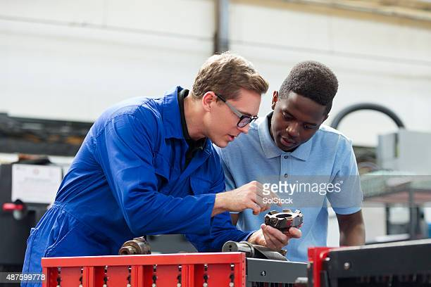 Apprentice Machinist Learning from Fellow Worker
