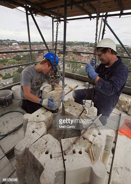 Apprentice mason Andrew Kirby and stonemason Gerald Wilson position and set new stonework on a spire on the roof of the north transept at Salisbury...